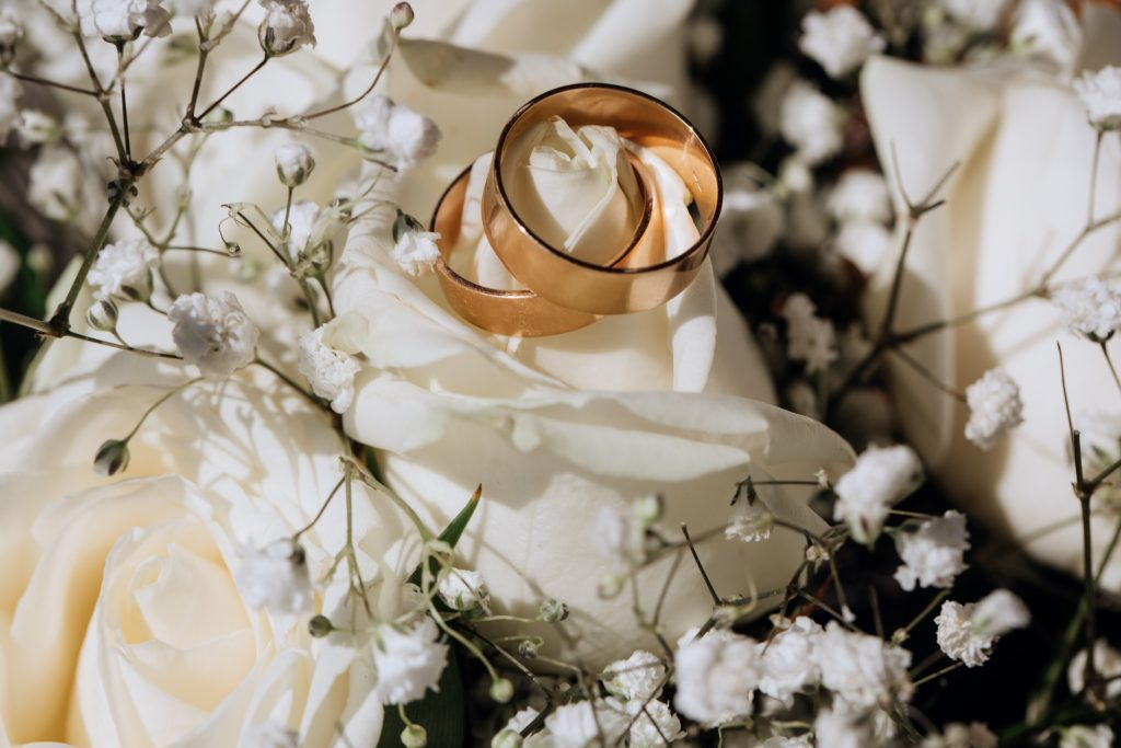Golden wedding rings on the white rose  from the wedding bouquet